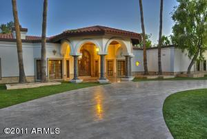 Travertine drive with Canterra stone encased front entry 15' dbl iron doors.