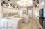 Big eat-in island kitchen opens to the family room and has bleached oak cabinetry, a Sub-Zero fridge with cabinet front, built-in oven, pantry, desk, and oversized tile floors. Breakfast area with bay windows overlooks the back yard.