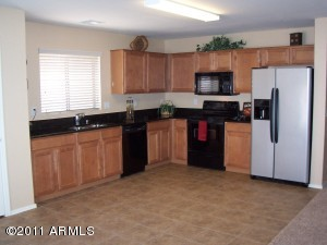 Gourmet kitchen w/Granite Slab countertops,Maple spice cabinets, Black appliances,SS undermount sink, refrigerator, soap dispenser & large pantry.