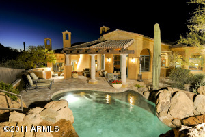 Through out the exterior randomly placed and colored pinion cantera stone tiles are pitted to give an old world flavor similar to old world pavers found in a European Village. Spectacularly designed Boulder grotto and waterfall are the highlight of this gorgeous heated pool with pebble finish.