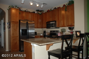 Beautiful Kitchen open to Dining and Family Room with Granite Countertops, b/i Microwave, flat-top range, black sink and beautiful spice maple cabinets.