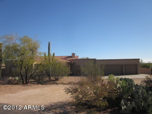 Front view of home with a circular drive and natural desert scape