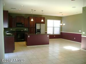 This kitchen is sure to delight any gourmet! Cherry cabinets, pendant lighting, black appliances, recycling center, granite counters!