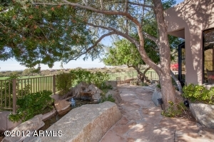 Marvelous outdoor patio with flagstone, shade trees and a water feature.
