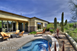 Beautiful backyard oasis w/ covered patio w/ stacked stone detail, oversized spa w/ water feature and Mountain Views!
