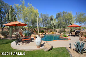 Exceptional outdoor living space describes this lush backyard. Owner very proud of 5 stately Saguaros, beautifully maintained annuals, pebble-tec pool, covered patio, barbeque station, and much more.