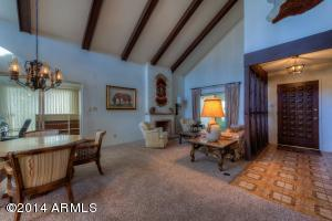 Living room with vaulted beam, ceiling and gas fireplace. Foyer and front door.