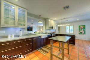 Solid wood lower cabinets, under cabinet lighting and built-in trash recycling are just a few of tasteful amenities of this open and spacious kitchen.