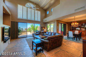 A fabulous great room with flagstone floors and soaring ceilings has a wood burning fireplace and sliding door to the patio.
