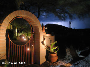 Dramatic courtyard entry while evening storms are in the distance. Magical views and privacy are everywhere in this hillside home