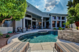 Sparkling swimming pool looking to the home and covered patio