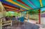 The cheerfully colored, covered patio offers plenty of shade to enjoy the lush fruit/vegetable/herb gardens that surround the pool.