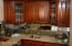 Full wet bar and service counter of slab granite and custom made cherry cabinets in a rich stain.