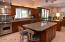 A true island with under mount sink, generous space between cabinets and abundant custom designed cherry wood cabinetry.