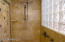 Wonderful shower with glass door and natural stone finishes.