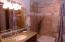 Private bath with granite, stonework shower and linen storage.