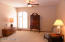 Large room with 10 ft ceilings and dual sided dressing room before entry to bathroom.