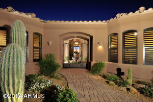 Cobblestone paved sidewalk leads you to gated courtyard entry with custom wrought iron gate.