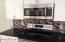 View of stove, microwave and tiled backsplash