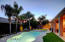 Well lit and manicured landscape with a sparkling pool