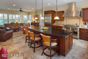 Fully remodeled kitchen with Granite slab island and slab counters,cherry cabinetry, stainless commercial grade oven and range with built-in refrigerator