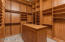 A very large closet with floor to ceiling custom shelving and an island.