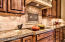 Notice the classic beauty of the accent tiles on the backsplash and range hood.