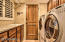The downstairs laundry room features lots of storage space, a utility sink, and counter space for folding laundry.