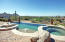 Negative edge pool with elevated spa, attached fountain, LED Lighting in pool and spa, and gas fire pots on either side.