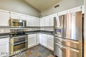 Large kitchen opens to dining area and living room, features center island and stainless steel appliances.