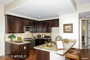 Kitchen with gas cooktop, granite and breakfast bar.
