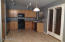 Eat-In-Kitchen. Black Appliances, Tile Flooring, French Doors to Covered Patio & Lush Green Backyard.