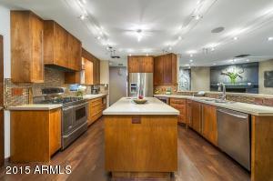 2 sinks, flat panel cabinets w/ built in organizers, stainless appliances, 6 burner gas range w/ wood panel hood, wine fridge.