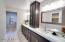 Master bathroom has dual sinks, walk in closet, oversized walk in shower with marble tile walls and floor