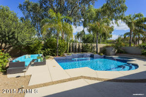 Stunning backyard rivals any resort with tiled pool and spa, firepit, and patio ready for cool nights with both ceiling heater and heated tile floor!