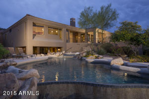 Professionally landscaped backyard with golf course, sunset, and city light views.