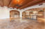 """another view of the spacious great room looking toward the kitchen and wet bar area. All living areas throughout the home feature beautiful 24"""" chiseled edge Noche travertine floors."""