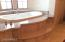 A close up of the marble surround soaking tub. Tub is insulated and has whirlpool controls.
