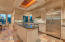 Stylish kitchen with built in refrigerator, marble counter with gold flecks sparkle in the lights creating beautiful reflections.