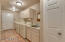 Generous laundry room from garage entry with upper and lower cabinets, wash sink, two storage closets.