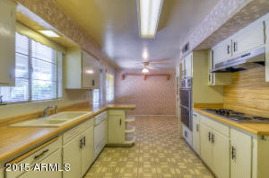 Galley-style kitchen has a counter top stove with plenty of counter and cabinet space.