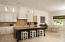 Open floor plan with ample light due to large windows and the detailed lighting package. Upgraded custom distressed finish cabinetry, some with glass fronts in the kitchen.
