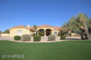 Front of home with large grassy area and dramatic curb appeal.