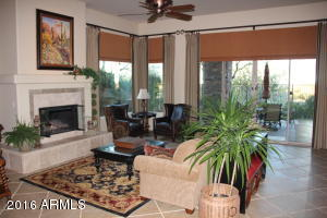 The formal living room, with gas fireplace, opens to your private patio and pool with amazing views of sunsets and city lights.