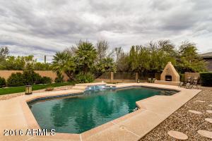 Large lot and beautiful pebble-tec pool looks toward Fireplace Kiva