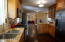 """42"""" upper cabinets with glass fronts & crown molding, granite counters, breakfast bar, nook & stainless steel appliances."""