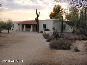 Front view showing circular drive, natural vegetation, and deep covered front entrance with saguaro to the side.