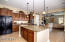 Cinnamon cabinets, upgraded granite, pendant lights and walk-in pantry.