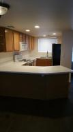 Kitchen with built in microwave and stainless steel refrigerator