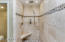 Large master shower, travertine with natural stone floor and decorative border